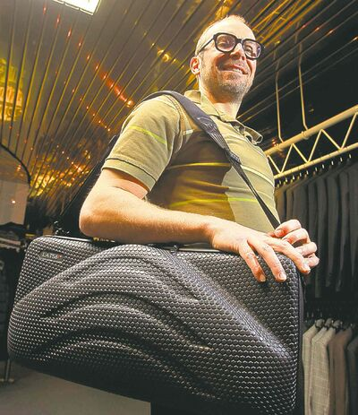Fashion. Threads. At  Hanford Drewitt, Jon Thiessen of UN Luggage, demonstrates how to travel light. He is using the Lat56 suit-carrier to pack a Boss Travel suit that costs $1,450.00 .  Wayne Glowacki / Winnipeg Free Press Oct. 22 2013