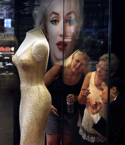 Leslie Kasperowicz (from left), Elaine Horrocks and security guard Lisa Ironstand look at Marilyn Monroe's diamond-encrusted, rhinestone-emblazoned evening gown on display Friday at the Save-On-Foods Northgate location. (Wayne Glowacki / Winnipeg Free Press)</p>