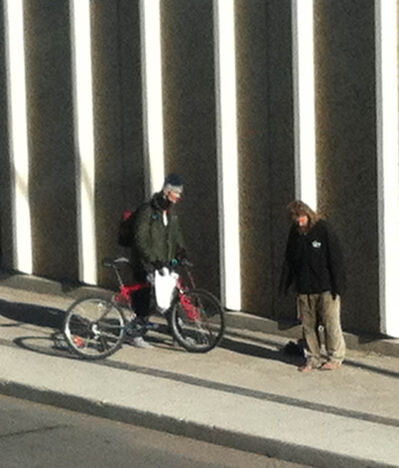 A cyclist gives away his shoes.