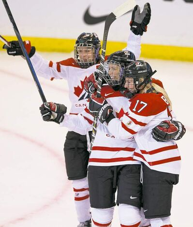 Canada's Catherine Ward (top) and Gillian Apps (centre) congratulate Bailey Bram on her first-period goal against Finland Friday night.