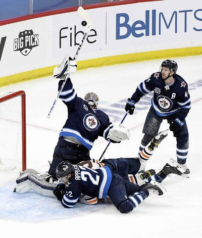 Winnipeg Jets goaltender Connor Hellebuyck (37) reaches for a bouncing puck after a shot during the second period. (Fred Greenslade / The Canadian Press)