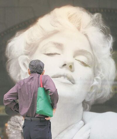 A man looks at a Marilyn Monroe picture outside a boutique in Tokyo. What is the universal attraction 50 years later?