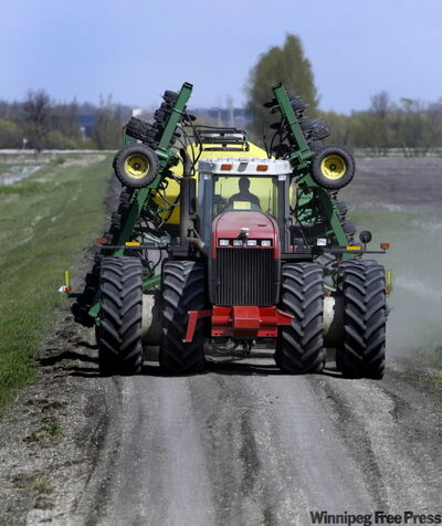 A farmer moves seeding gear between fields near La Salle last week. He's one of the lucky ones.