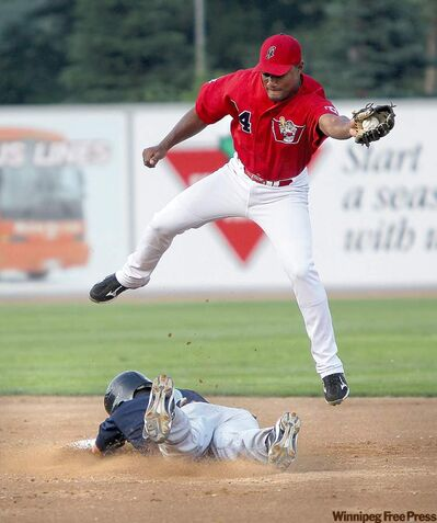 Goldeyes' Price Kendall reaches high to catch the ball while Rockford RiverHawks' Jake Eigsti slides into second in their game Thursday night at Canwest Park. RiverHawks won 7-1.