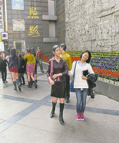 Duanduan Liu poses with one of the statues of shoppers at the entrance to Chunxi Road shopping zone.