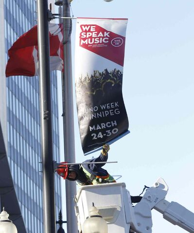 Shane Goertzen attaches the first official Juno Awards banner on Portage Avenue at Donald Street Tuesday morning. The annual Canadian music awards ceremony will take place in Winnipeg this year.