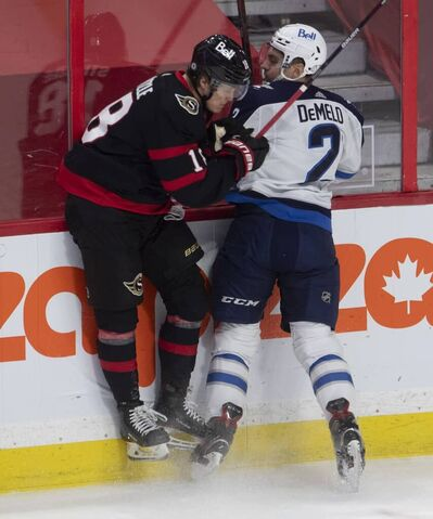 Ottawa Senators left wing Tim Stützle collides with Winnipeg Jets defenceman Dylan DeMelo along the boards during the first period. THE CANADIAN PRESS/Adrian Wyld