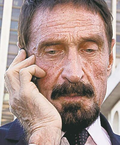 "Software company founder John McAfee talks on his mobile phone after a press conference outside the Supreme Court in Guatemala City, Tuesday, Dec. 4, 2012. McAfee, 67, who has been identified as a ""person of interest"" in the killing of his neighbor in Belize, 52-year-old Gregory Faull, has surfaced in public for the first time in weeks, saying Tuesday that he plans to ask for asylum in Guatemala because he fears persecution in Belize. (AP Photo/Moises Castillo)"