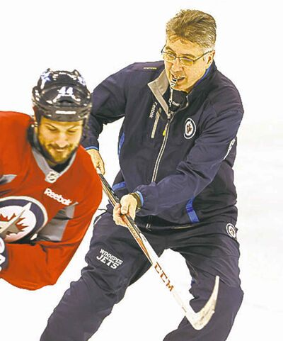 Head coach Claude Noel lays a little lumber on defenceman Zach Bogosian Thursday at practice.
