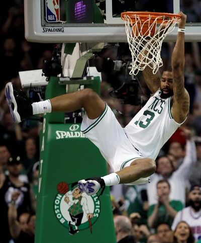 Boston Celtics forward Marcus Morris hangs from the rim after dunking against the Cleveland Cavaliers during the first half in Game 2 of the NBA basketball Eastern Conference finals Tuesday, May 15, 2018, in Boston. (AP Photo/Charles Krupa)
