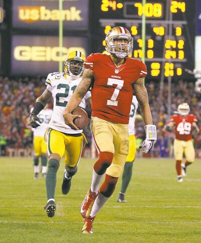 The San Francisco 49ers� Colin Kaerpernick (7) beats the Green Bay Packers� Charles Woodson (21) to end zone for a touchdown in the NFC Divisional Playoff on Saturday, January 12, 2013, at Candlestick Park in San Francisco, California. The Niners worn, 45-31, as Kaerpernick ran for two TDs and passed for two more. (Rick Wood/Milwaukee Journal Sentinel/MCT)