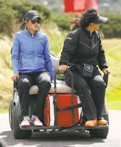 Scott Heppell / the associated pressMichelle Wie (left) is driven back to the clubhouse after the wind stopped play during the third round of the Women�s British Open tournament.