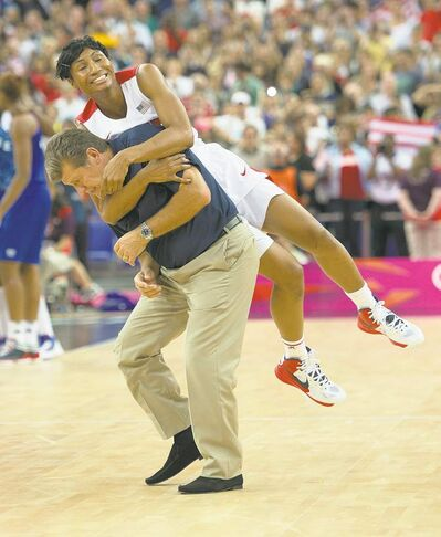 Harry E. Walker / MCTAngel McCoughtry tackles unsuspecting U.S. coach Geno Auriemma after defeating France for basketball gold.