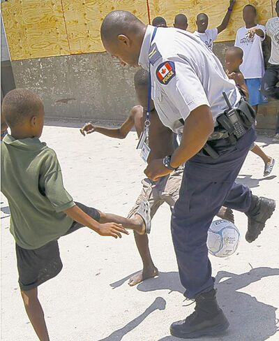 Cpl. Gilbert Saillant kicks the ball around with young boys in Haiti.