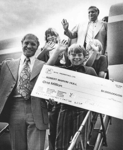 Ben Hatskin (back) waves as a dapper Bobby Hull and his family display his million-dollar cheque.