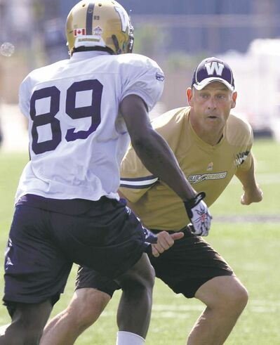 Blue Bombers offensive co-ordinator Gary Crowton works with slotback Clarence Denmark at practice Wednesday.