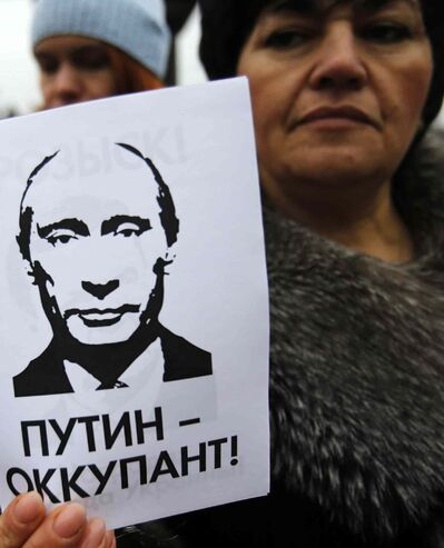 "A woman holds a banner that reads: ""Putin is Occupier"" during a rally against the breakup of the country in Simferopol, Crimea, Ukraine, Tuesday, March 11, 2014."