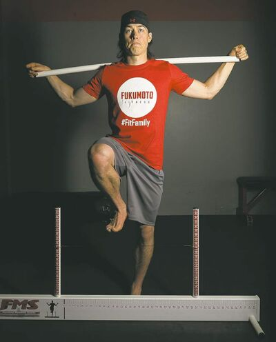 Johnny Fukumoto demonstrates a hurdle step over the Functional Movement System as part of a fitness assessment.