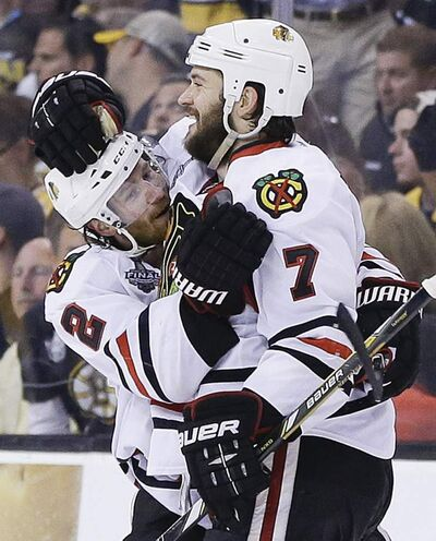 Chicago Blackhawks defenceman Brent Seabrook (7) celebrates his game-winning goal with teammate Duncan Keith Wednesday night.