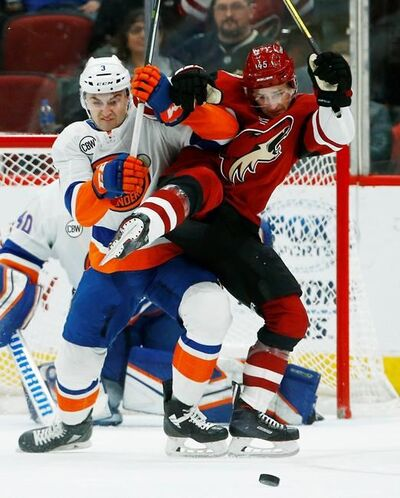 New York Islanders defenseman Adam Pelech (3) battles with Arizona Coyotes right wing Josh Archibald (45) during the first period of an NHL hockey game Tuesday, Dec. 18, 2018, in Glendale, Ariz. (AP Photo/Ross D. Franklin)