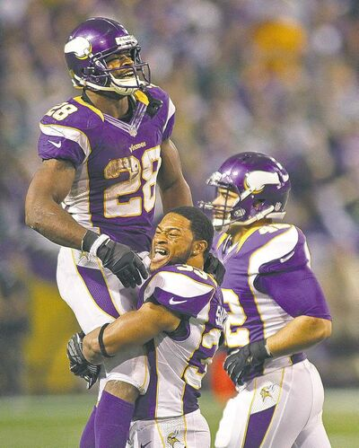 Minnesota Vikings running back Adrian Peterson (28) is lifted by teammate Jamarca Sanford after leaving the field against the Green Bay Packers Sunday. Peterson didn't catch Eric Dickerson's rushing record, but he did set up the winning field goal.