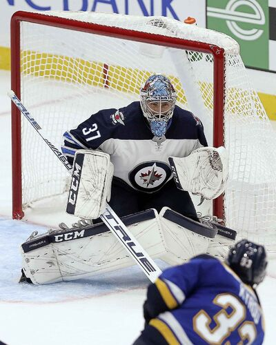 Winnipeg Jets goaltender Connor Hellebuyck (37) protects the goal from a shot from St. Louis Blues center Jordan Kyrou (33) during the third period of an NHL hockey game Thursday, Oct. 4, 2018, in St. Louis. (AP Photo/Scott Kane)