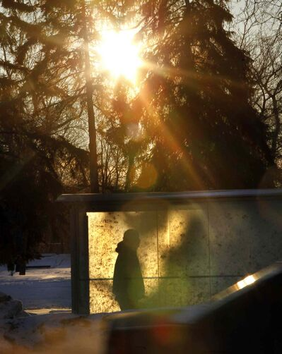 A transit rider takes shelter on Main Street as the sun rises on another cold -25 C Monday morning.