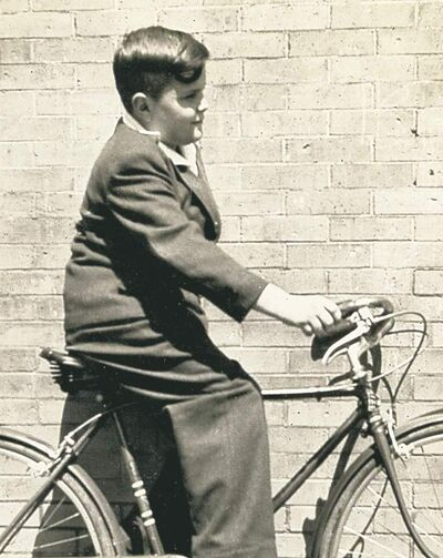 A young John Kennedy Toole rides his bike in New Orleans.