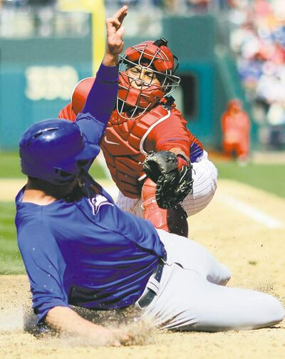 Matt Slocum / the associated pressToronto Blue Jays� Ryan Langerhans (bottom) scores under the tag from Philadelphia Phillies catcher Carlos Ruiz on a two-run double by Mike Nickeas in the ninth inning Saturday.