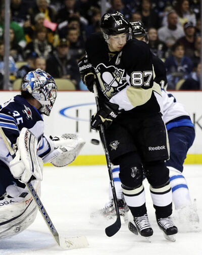 Pittsburgh Penguins centre Sidney Crosby (87) cannot deflect a shot in front of Winnipeg Jets goalie Al Montoya (35) during the second period of an NHL hockey game in Pittsburgh, Thursday. The Penguins beat the Jets 4-0.