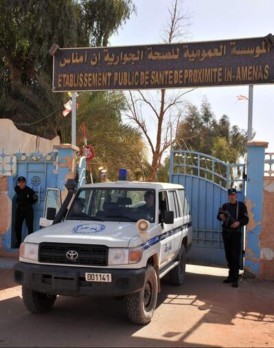 Algerian police guard the entrance of a hospital near the gas plant where hostages have been kidnapped.