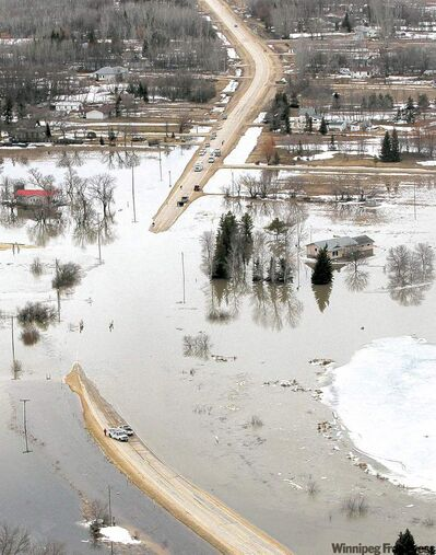 MIKE.DEAL@FREEPRESS.MB.CA A house with a breached dike sits near the flooded Breezy Point Road north of Selkirk Friday.