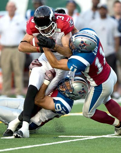 Calgary's Brad Sinopoli is hauled down by Alouettes linebacker Chip Cox.