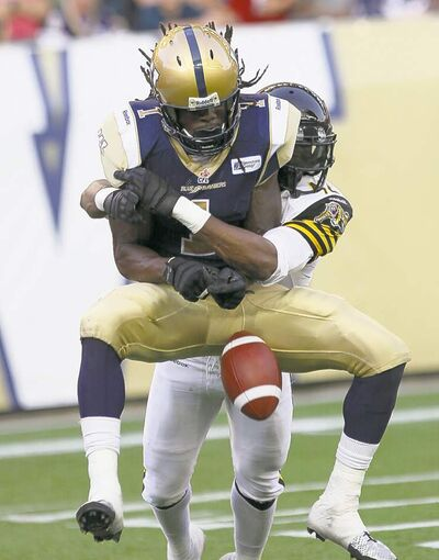 Winnipeg Blue Bombers Kito Poblah is plastered by Hamilton Tiger Cats Raymond Brown in the end zone (left).