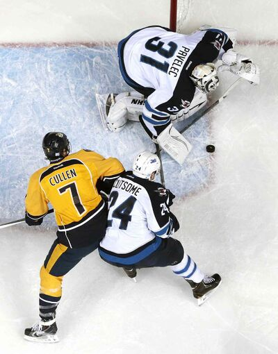 Winnipeg goalie Ondrej Pavelec blocks a shot as Jets D-man Grant Clitsome steers Nashville forward Matt Cullen away from the rebound.