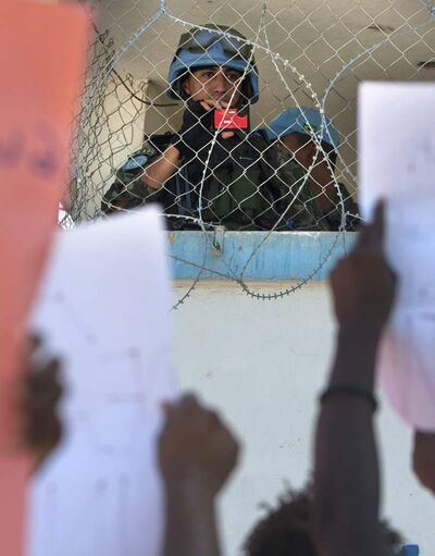 A member of Brazil's U.N. peacekeepers takes a picture of demonstrators during a protest against the United Nations peacekeeping mission, in Port-au-Prince, Haiti in October. The protest marked the second year since cholera was likely introduced to Haiti by a U.N. force and has gone on to kill more than 7,500 people and sicken more than 594,000 others.