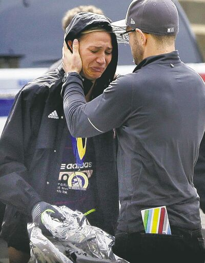 Elise Amendola / The Associated PressAn unidentified runner is comforted in the aftermath of the explosions.