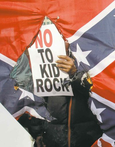 A protester is seen behind a burning Confederate flag; Kid Rock has come under fire for his use of the contentious symbol.