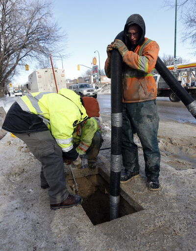 Workers prepare to thaw frozen water pipes on Mountain Avenue at Salter Street on Monday.