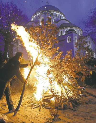 A man burns dried oak branches in a Serbian Orthodox Christmas Eve tradition.