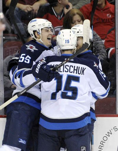 Winnipeg's Mark Scheifele (55) celebrates his first goal in weeks with linemates Matt Halischuk and Michael Frolik.