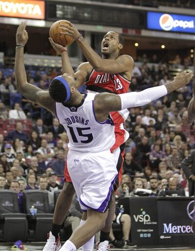 Portland Trail Blazers center Marcus Camby, top, drives to the basket and is fouled by Sacramento Kings center DeMarcus Cousins during the first quarter of an NBA basketball game in Sacramento, Calif., Thursday, Feb. 2, 2012. (AP Photo/Rich Pedroncelli)