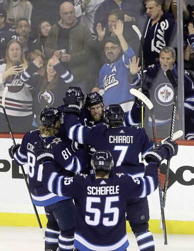 Winnipeg Jets players and fans celebrate with defenceman Joe Morrow after he scored against the New York Rangers during the third period in Winnipeg, Tuesday.