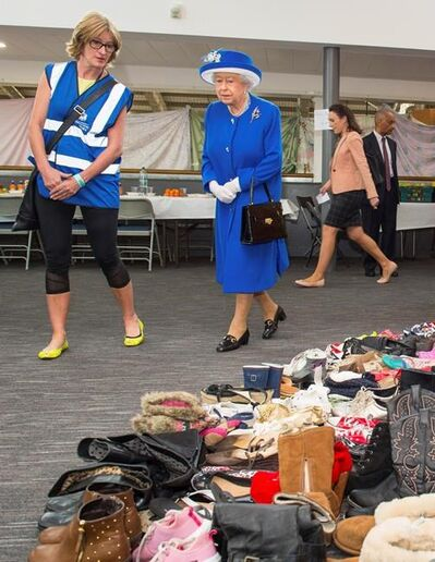 Executive Director of Kensington and Chelsea Council Sue Harris, left, shows Queen Elizabeth II donations of aid made by members of the local community during a visit to the Westway Sports Centre which is providing temporary shelter for those who have been made homeless by the fire at Grenfell Tower, in London, Friday June 16, 2017. Relatives of those missing after a high-rise tower blaze in London are searching frantically for their loved ones, as the police commander in charge of the investigation says he hopes the death toll will not rise to three figures. (Dominic Lipinski/Pool Photo via AP)