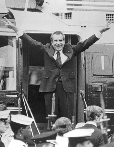 Nixon delivers his famous victory salute as he prepares to board a helicopter following his resignation.