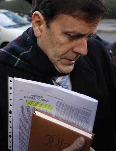 Doctor Eufemiano Fuentes carries papers reading 'Minister of healthcare. Royal Decree 1088/2005, of September 16, establish the technical requirements of the blood donation and transfusion centres and services�' as he arrives at a court house in Madrid, Spain, Monday, Jan. 28, 2013. The Operation Puerto doping-in-sport trial starts Monday where Judge Julia Santamaria will try six defendants, including doctors Eufemiano and Yolanda Fuentes and Jose Luis Merino, cycling team managers Manolo Saiz and Vicente Belda and trainer Ignacio Labarta. No athlete will sit in the dock, but many must appear as witnesses, including Alberto Contador. The trial ends March 22. (AP Photo/Andres Kudacki)