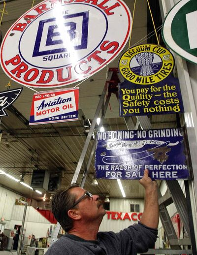 Bill Krasey gets some of the items ready for this weekends auction in Stonewall. McSherry Auction Service will be putting up for sale some highly sought-after gas station signs, vintage pumps and other memorabilia Sunday.