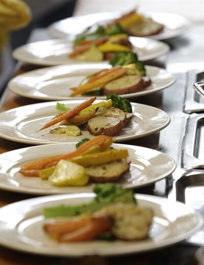 This Thursday, Aug. 11, 2011 photo shows plates of food lined up in the kitchen of FareStart, a program that helps troubled and homeless people by training them to work in the food industry, in Seattle. (AP Photo/Ted S. Warren)