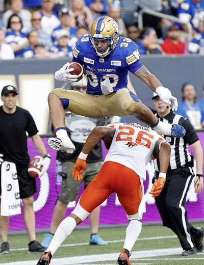 Winnipeg Blue Bombers' Andrew Harris leaps over BC Lions' Anthony Orange last Saturday.  Andrews ran for over 100 yards in the first half alone.
