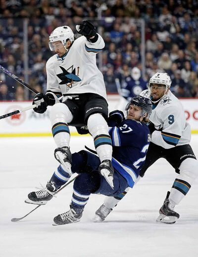 Winnipeg Jets' Nikolaj Ehlers and San Jose Sharks' Brenden Dillon collide as Evander Kane skates by during the second period.